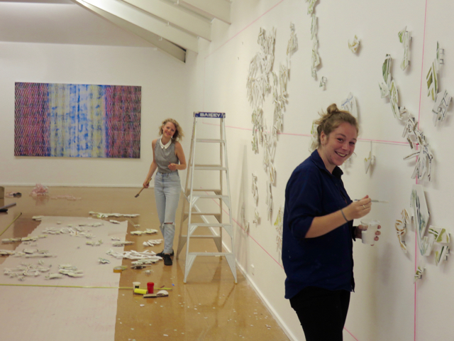 Hayley and Sabrina at work with work by Joel Arthur in the distance